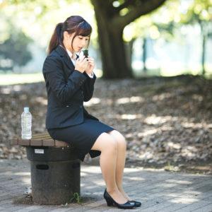 公園のベンチで食事をする女性