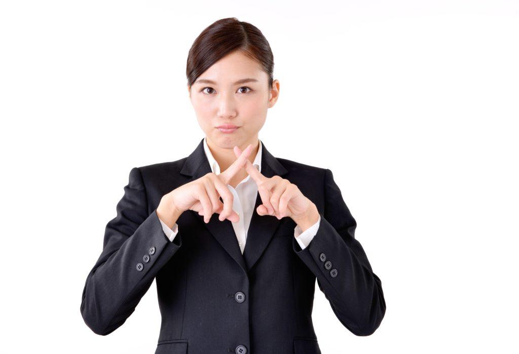 バツ印を出す女性の写真