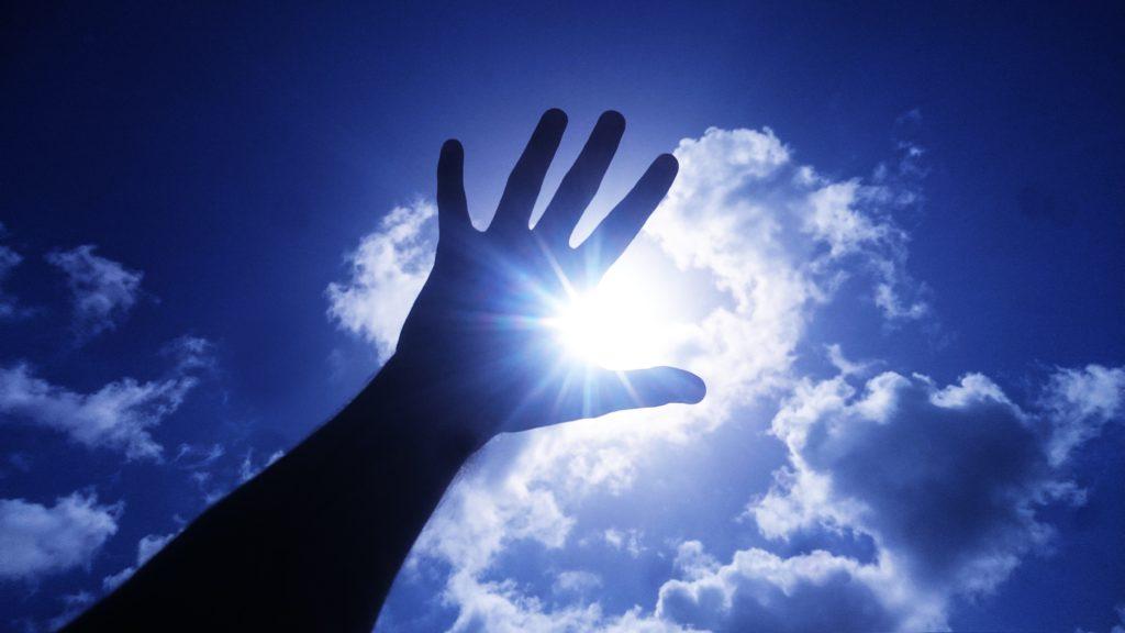 空に手をかざす写真