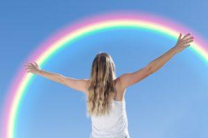 虹に向かって手を広げる女性