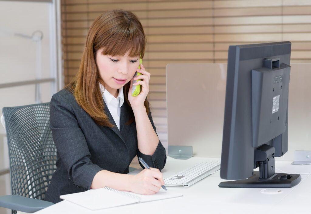 電話応対する女性の写真
