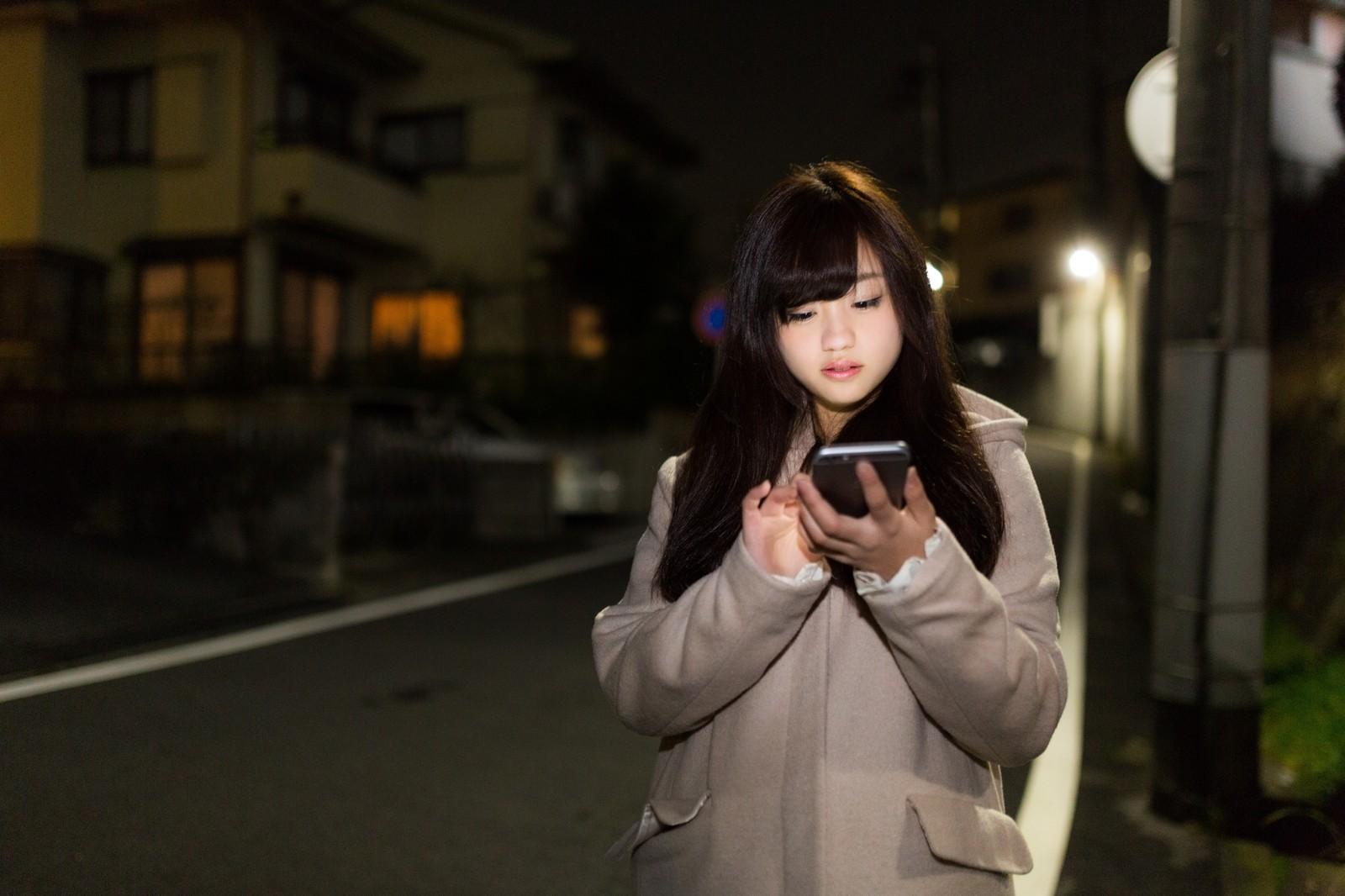 歩きスマホをする女性の写真