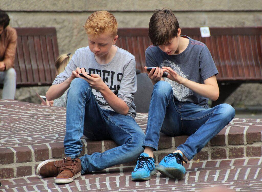 友達と一緒にいても会話ではなくスマートフォンを見ている子供たちの写真