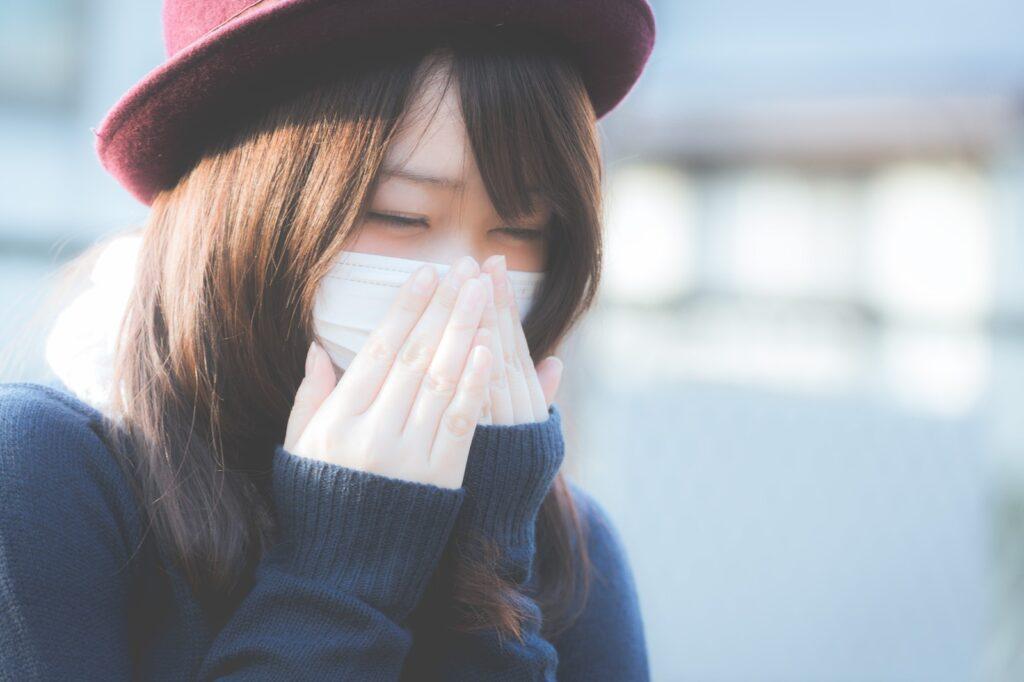マスクをしてくしゃみをする女性の写真